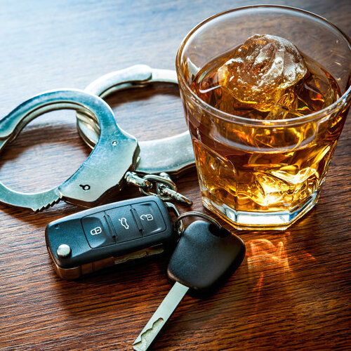 Glass of alcohol on a table next to car keys and handcuffs.