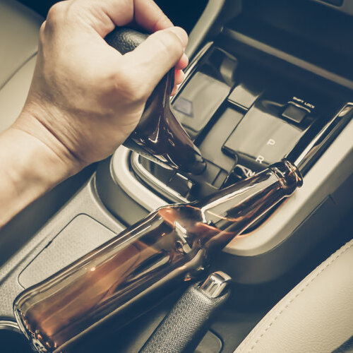 Hand holding a gear shift next to a bottle of alcohol.