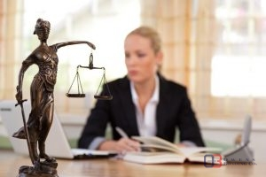 A Young Lawyer Sitting at a Desk with Lady Justice in Front of Her